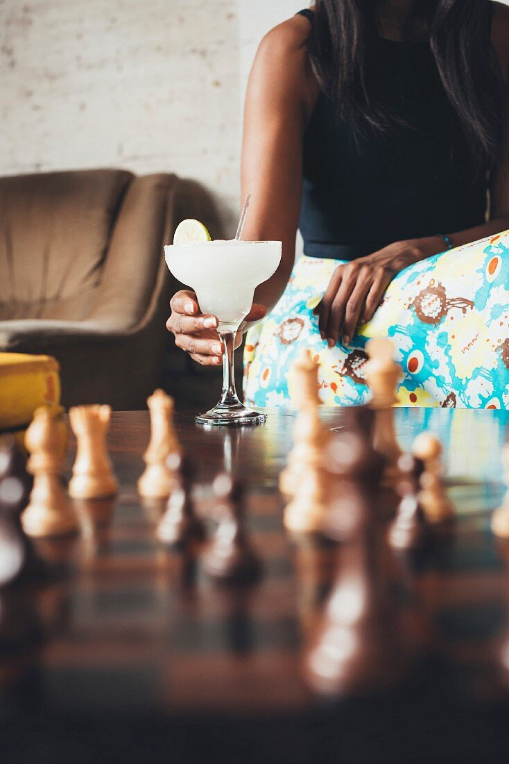 A dark-skinned woman with a cocktail sitting at a game of chess at the Potato Shed restaurant (Johannesburg, South Africa)
