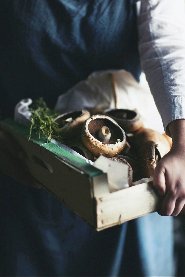A chef carrying a wooden box of mushrooms and herbs