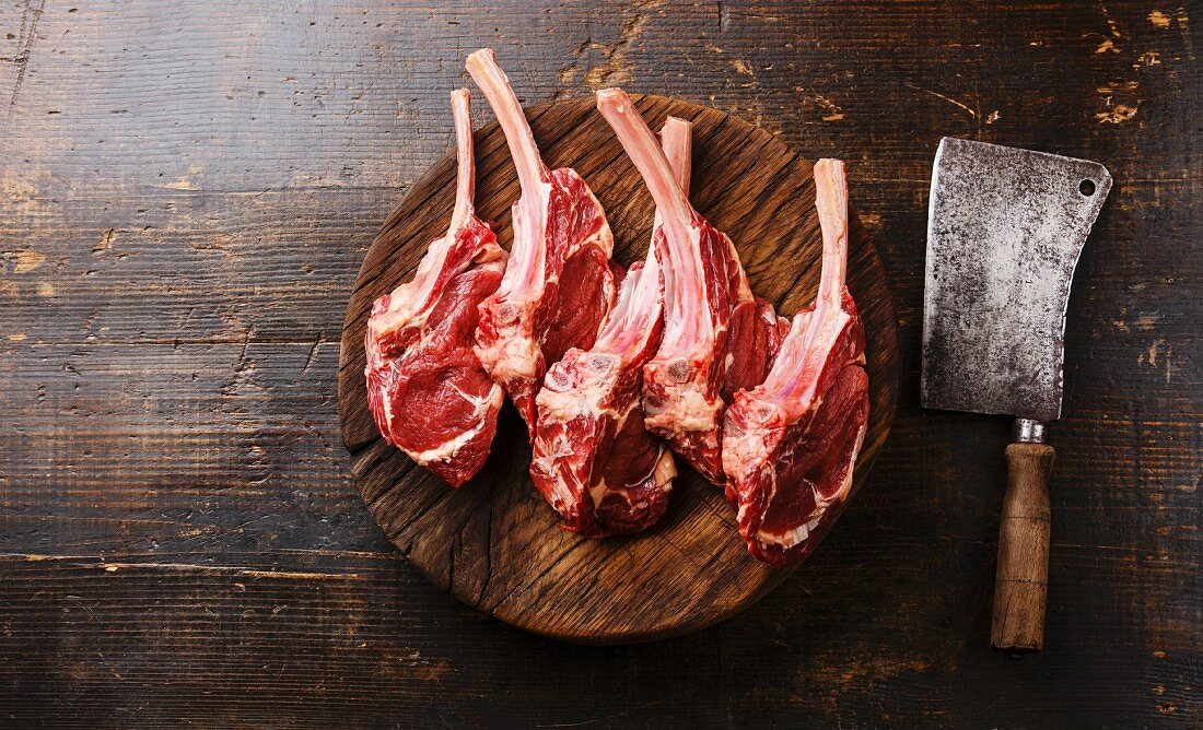 Raw fresh meat Veal ribs on butcher wooden block and Meat cleaver on wooden background