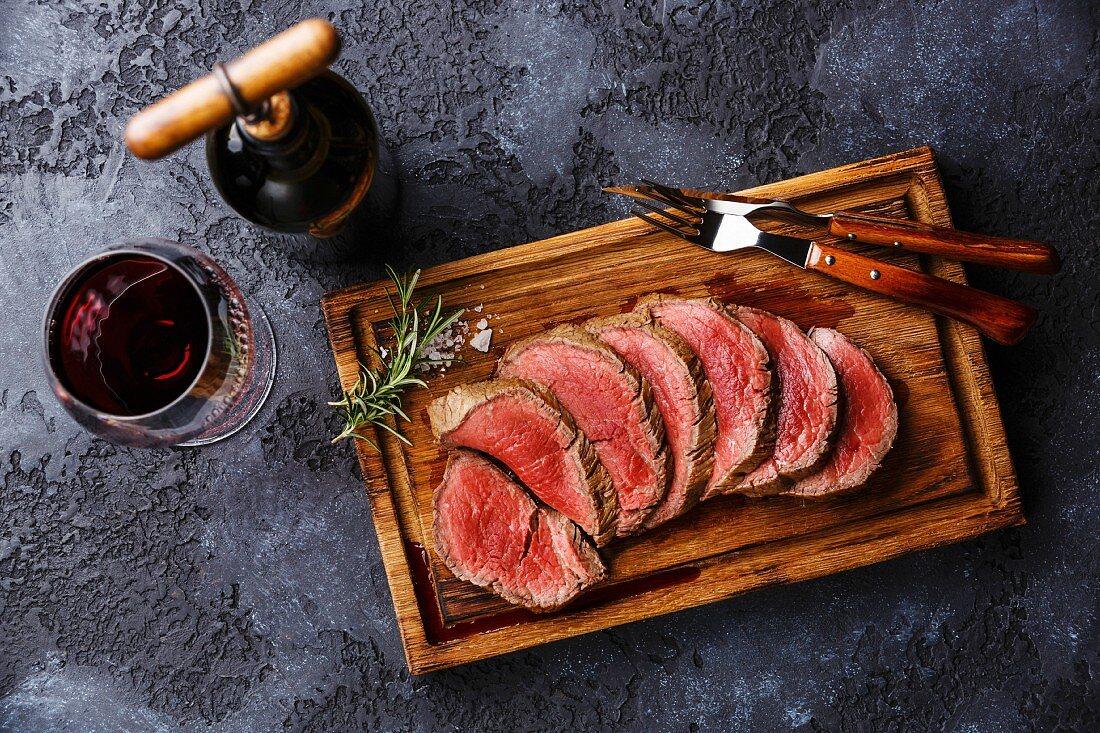 Sliced grilled tenderloin Steak roastbeef on wooden cutting board and Red wine on dark background