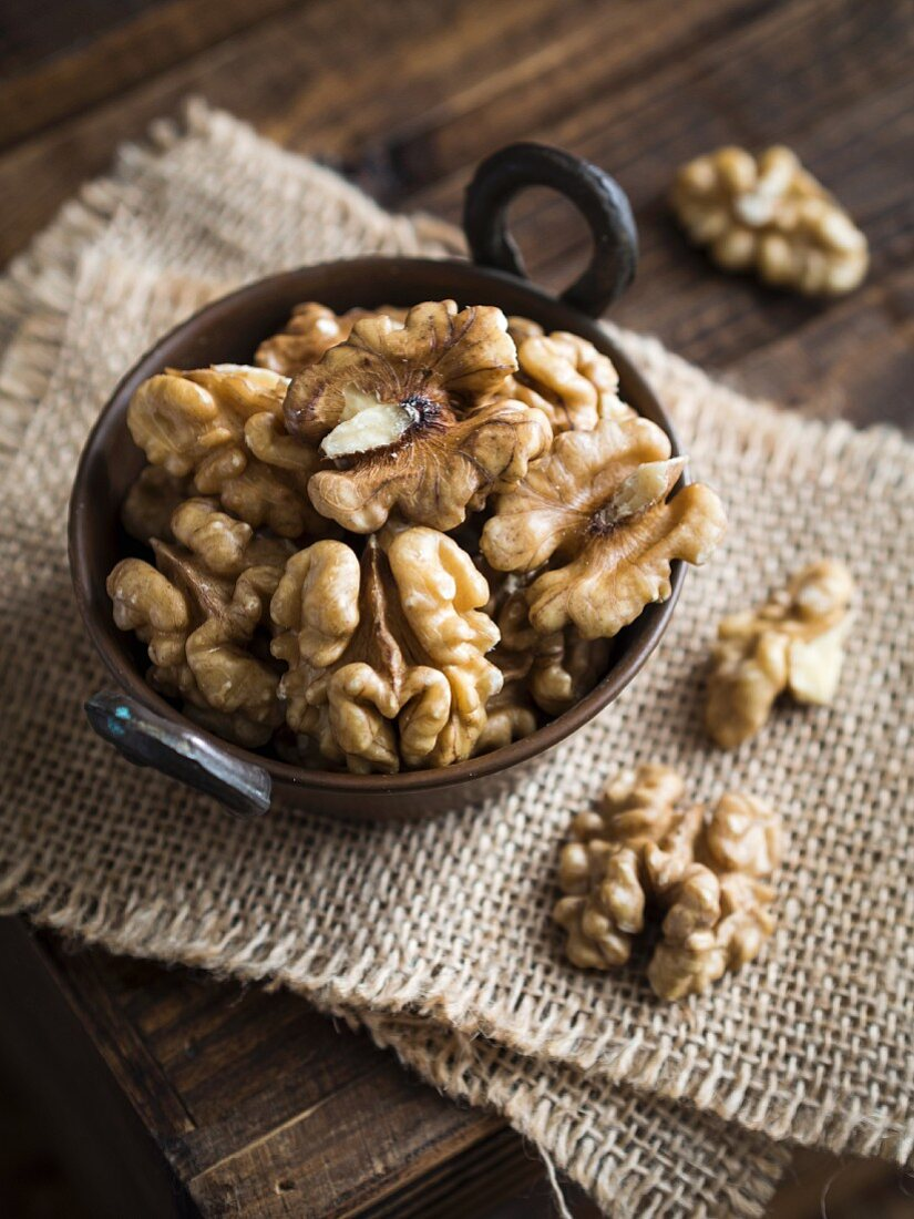 Walnuts in a small copper bowl on a wooden table
