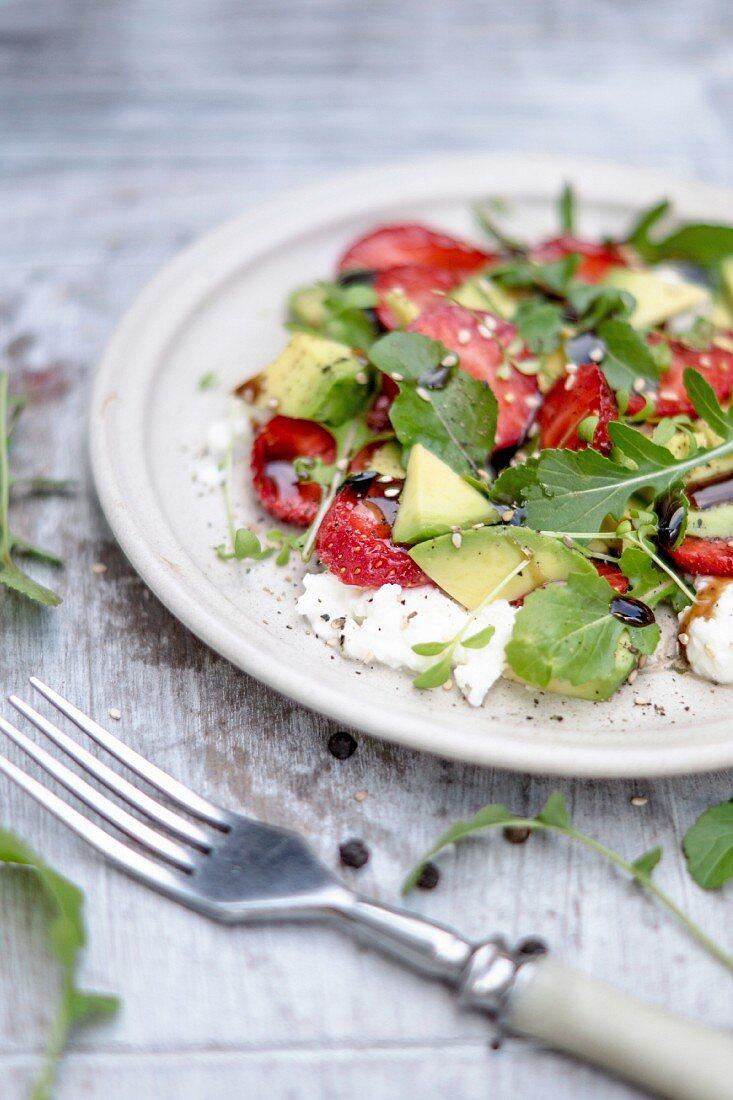 A salad with mozzarella, strawberries, avocado, sesame seeds and balsamic dressing