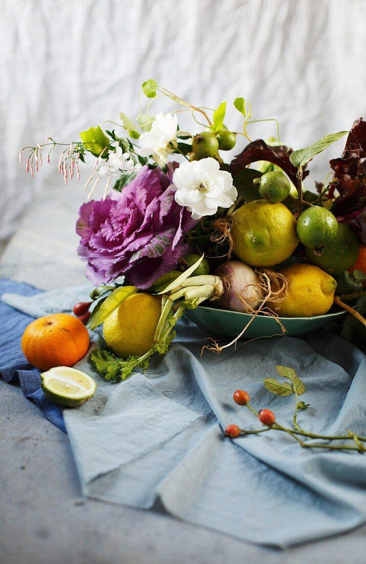Arrangement aus Blüten, Zweigen, Obst und Gemüse