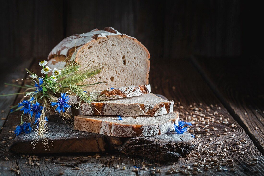 Sliced healthy wholemeal bread on a board with ears of corn and wild flowers