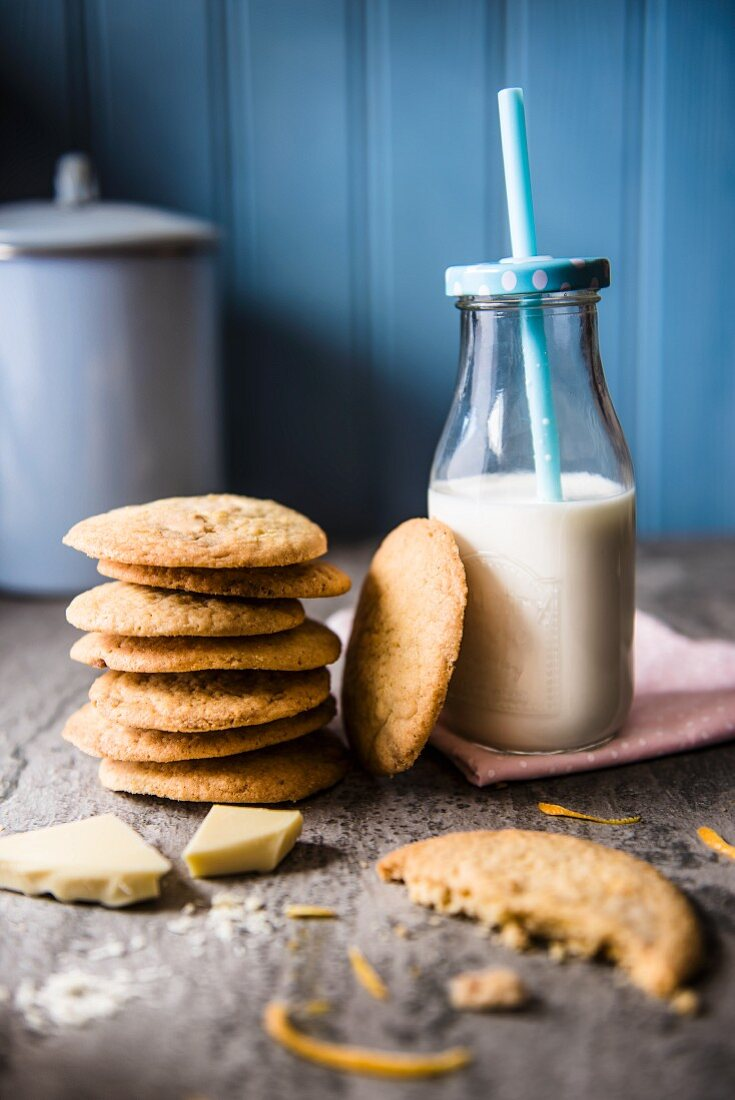 White chocolate and orange biscuits with a bottle of milk