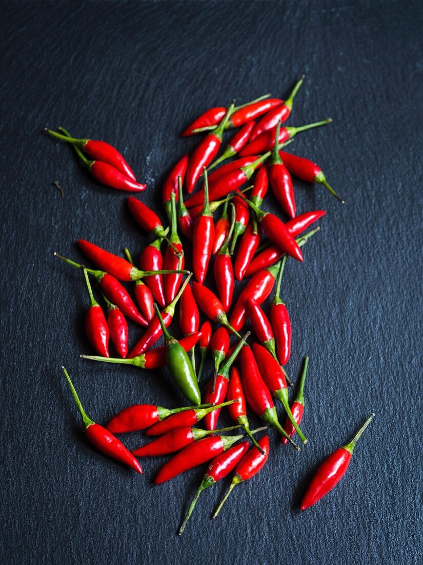 Small chilli peppers scattered on slate