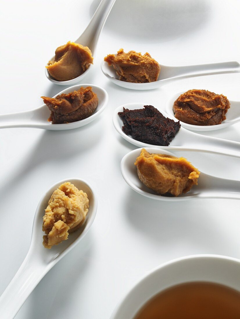 Several spoons containing different miso pastes