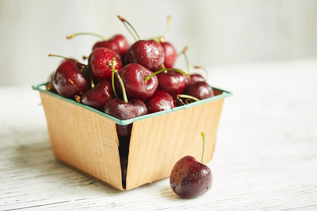 Cherries covered in water droplets in a punnet