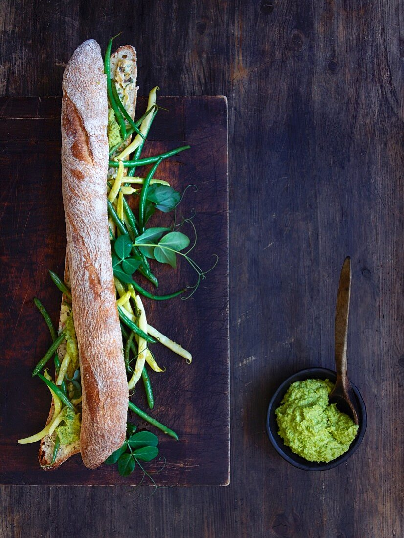 A baguette with bacon and thyme butter, beans, and sugar snap peas