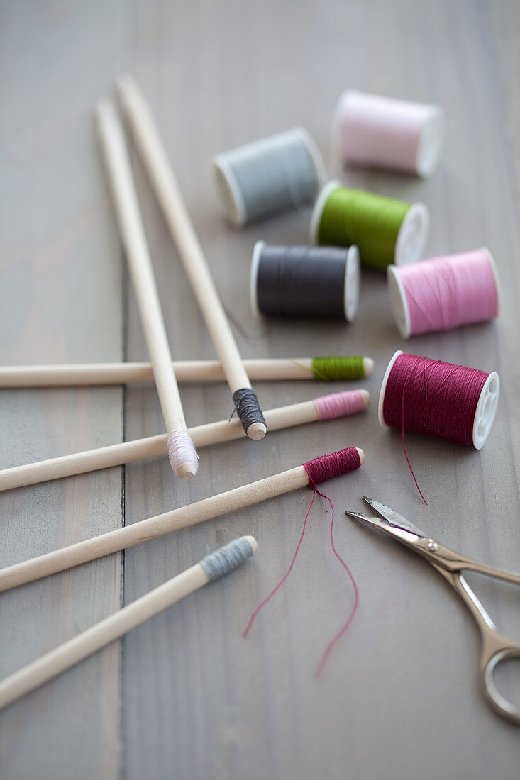 Different colours of thread wrapped around ends of wooden skewers