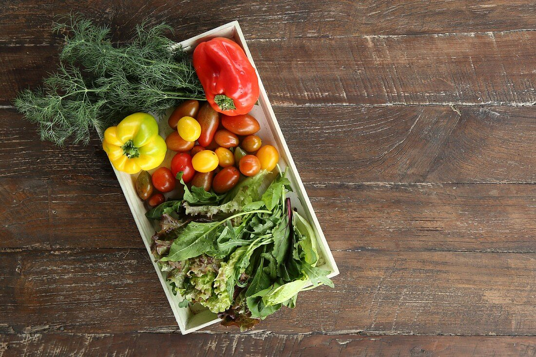Vegetables and salad on a wooden tray and wooden background (seen from above)