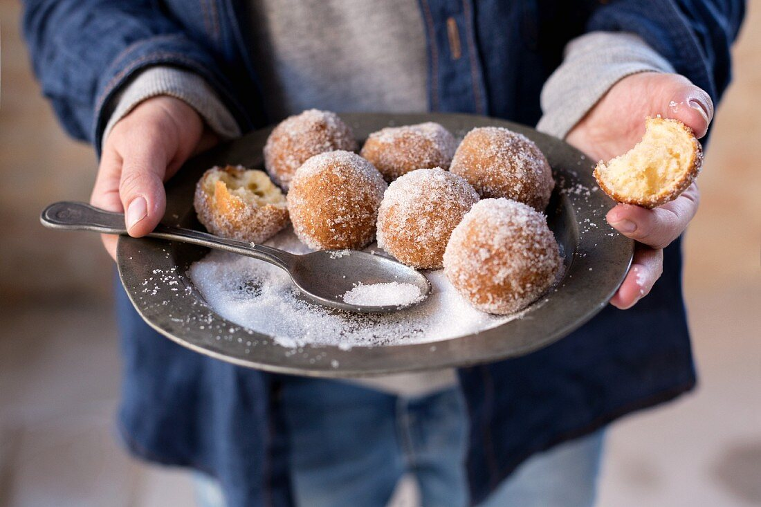 Hands holding a rustic pewter plate with sugared quark balls