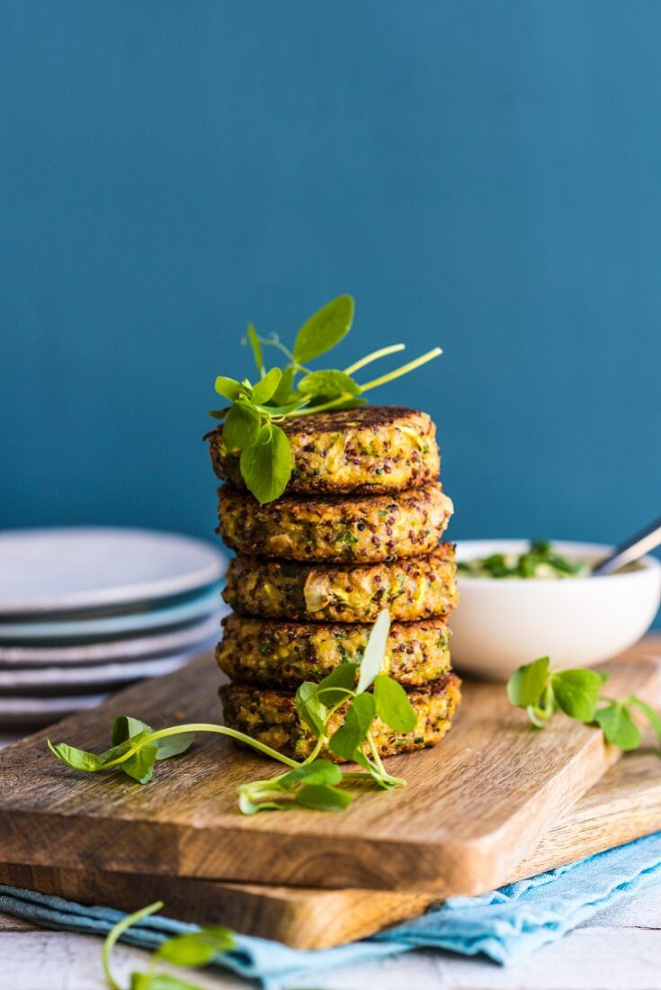 A stack of quinoa veggie fritters on a chopping board