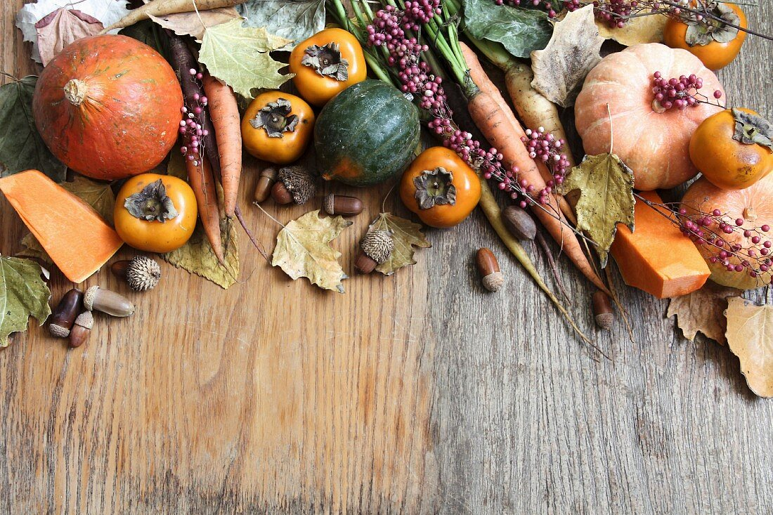 Assorted varieties of autumn vegetables and Japanese persimmon on a wooden surface