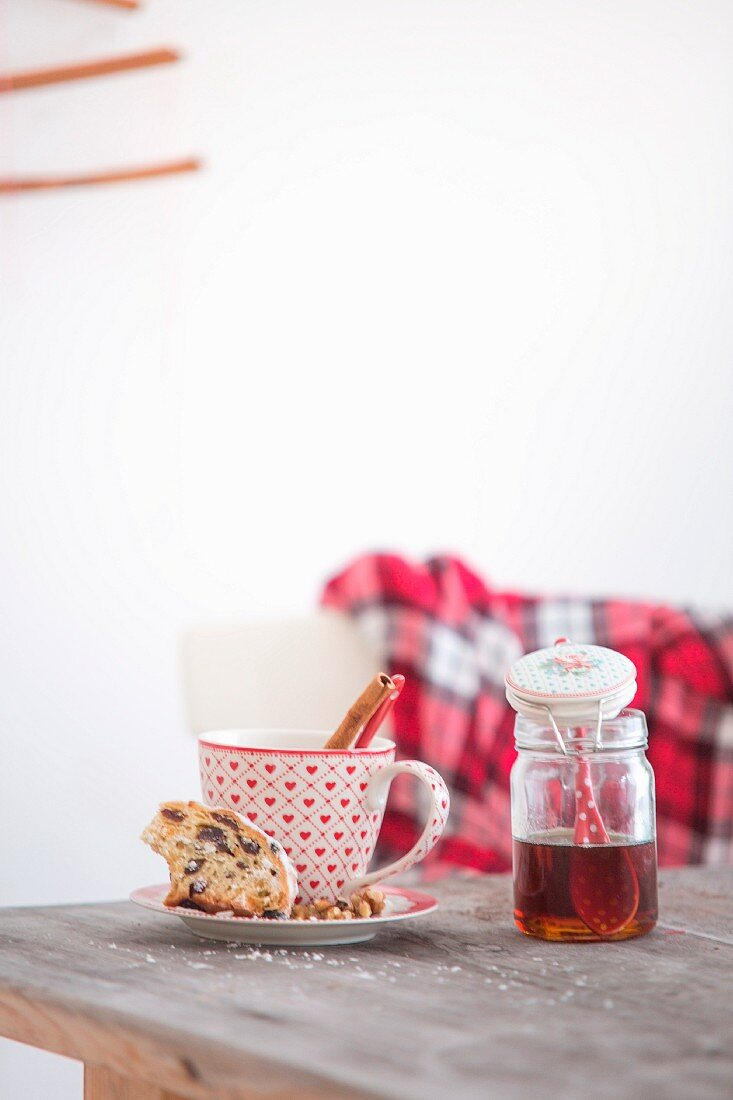 Stollen fruit cake, cinnamon stick in red and white cup and jar of honey on wooden table