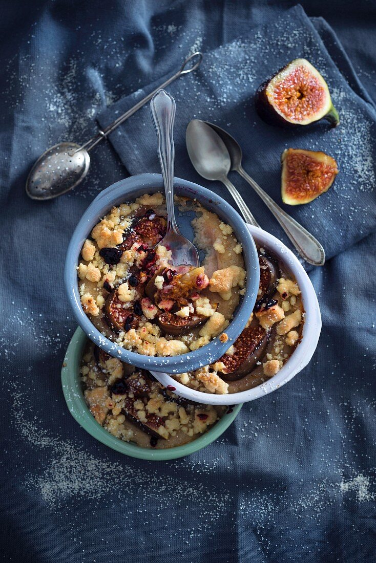 A stack of three ovenproof dishes of vegan baked semolina pudding with figs, a crumble topping and elderflower jam