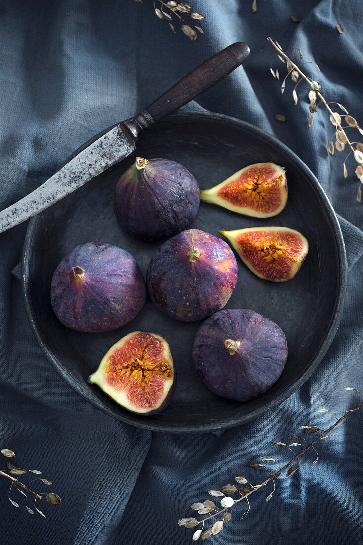 A bowl and a knife with four whole figs and one sliced fig