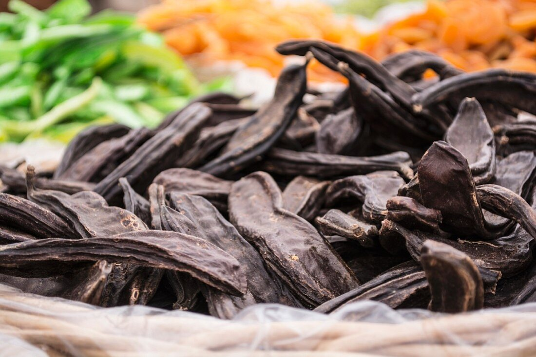 Carob pods in a basket at a market stall