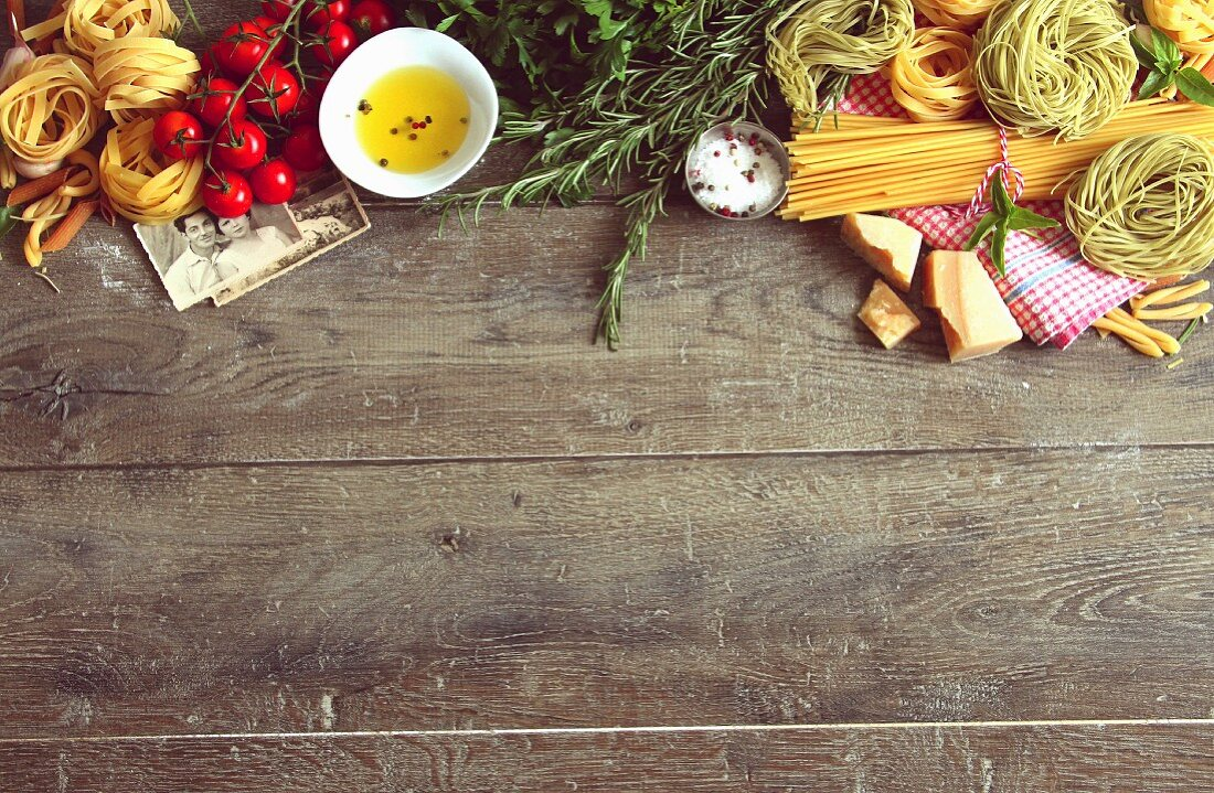 An arrangement of typical Italian food items and family photos on a wooden table