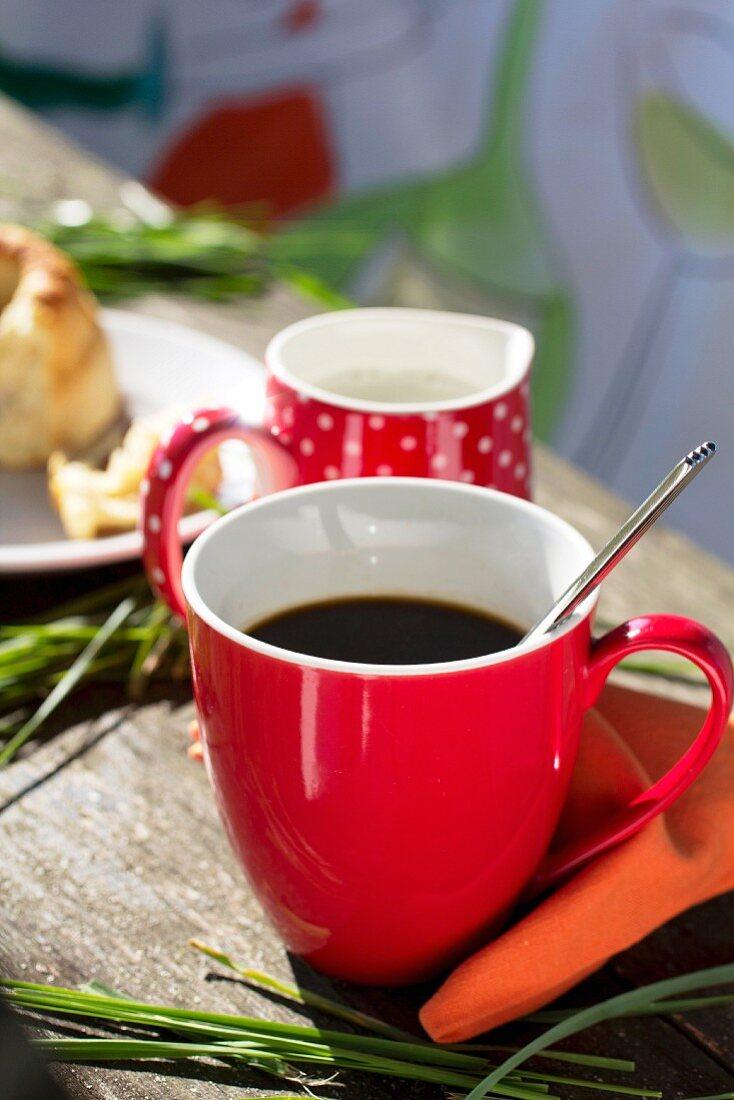 Red coffee cup, milk jug and orange serviette on wooden bench
