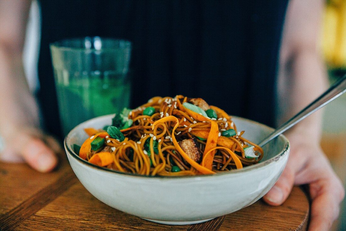 Wholegrain spaghetti with carrot strips and sesame seeds