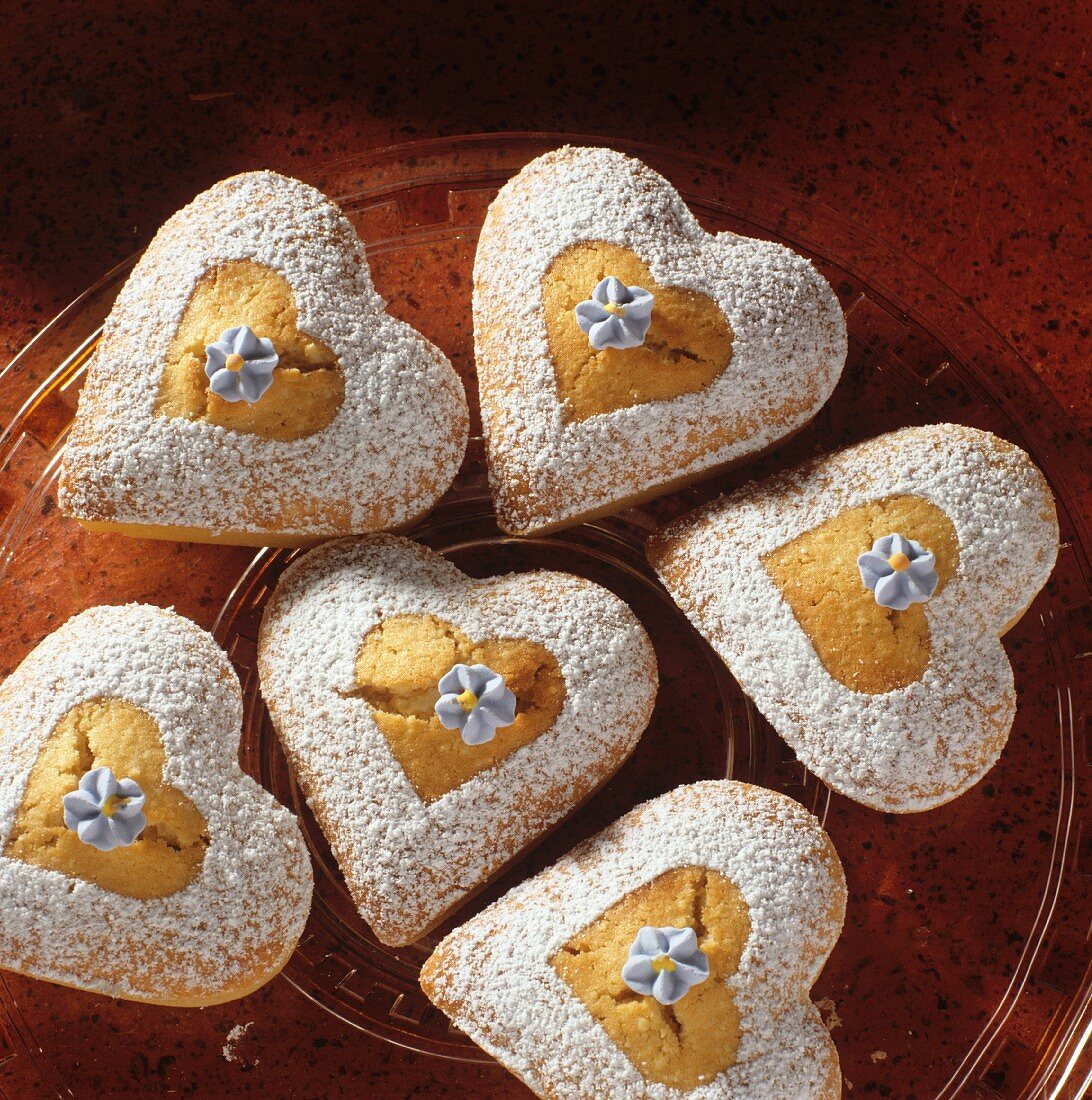Heart-shaped sponge cakes with icing sugar & sugar violets