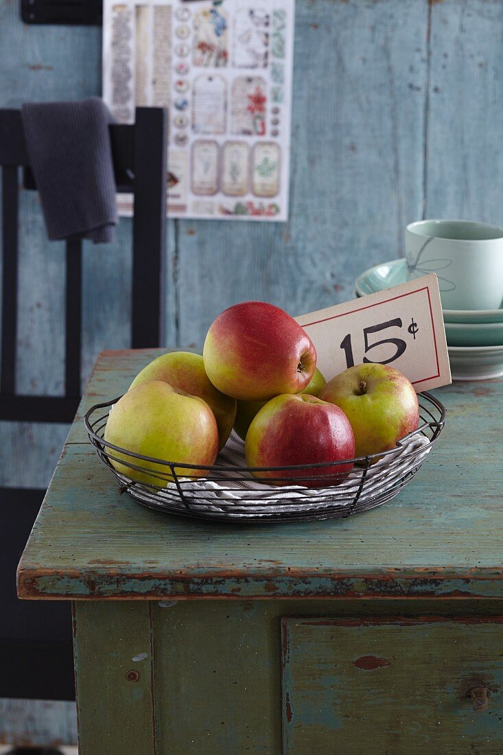Apples arranged in a wire basket on a wooden cabinet