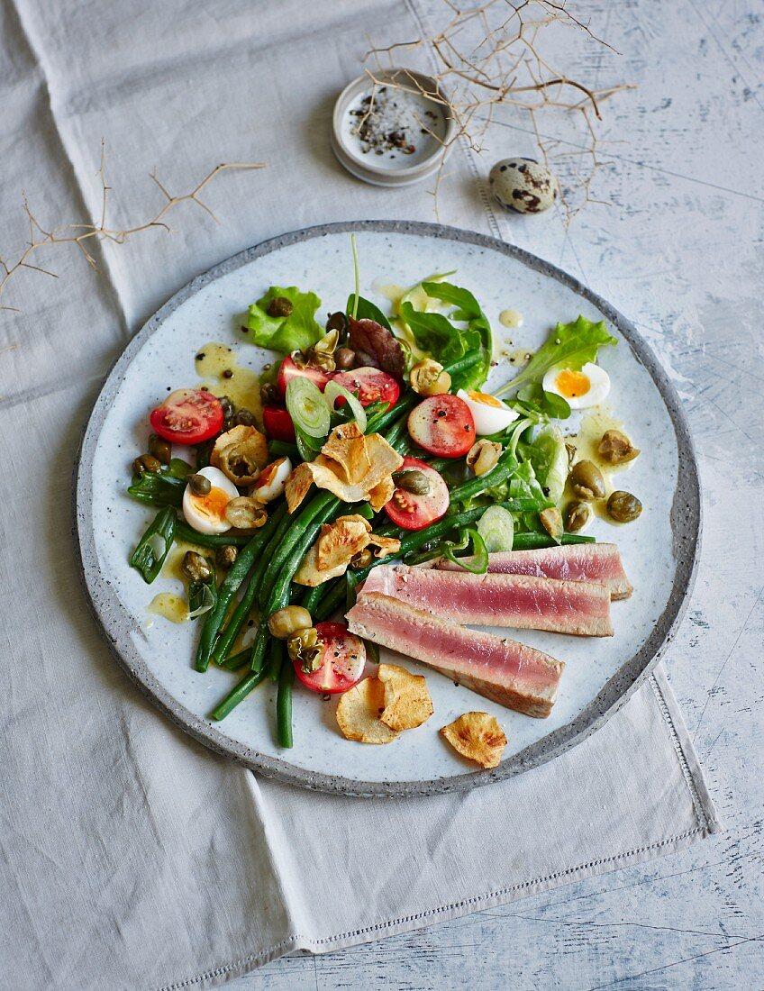 Salad niçoise with quail's eggs, tuna tataki and vegetable crisps (low carb)