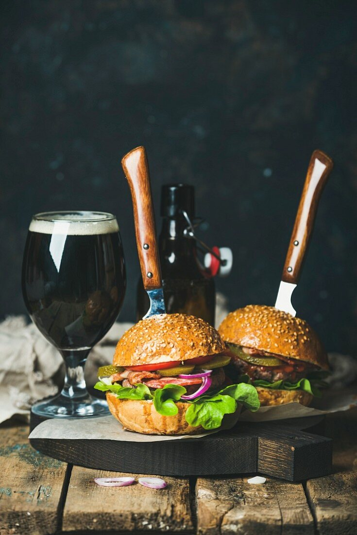 Homemade beef burgers with crispy bacon and fresh vegetables on serving board with glass of dark beer