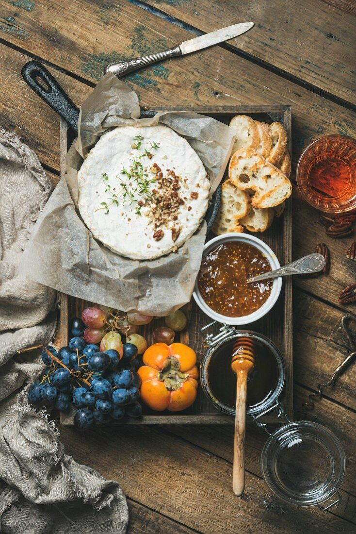 Camembert in small pan, grapes, persimmon, fig jam, honey, baguette slices and glass of rosé wine