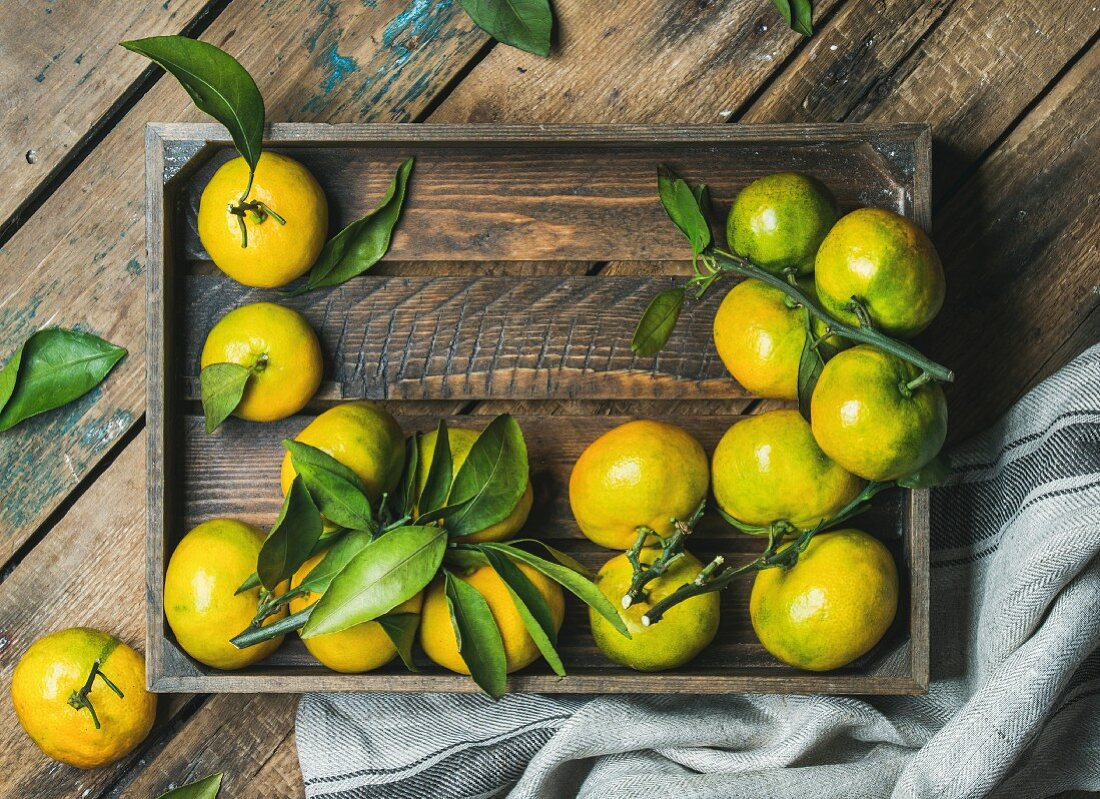 Fresh tangerines with leaves in a wooden box