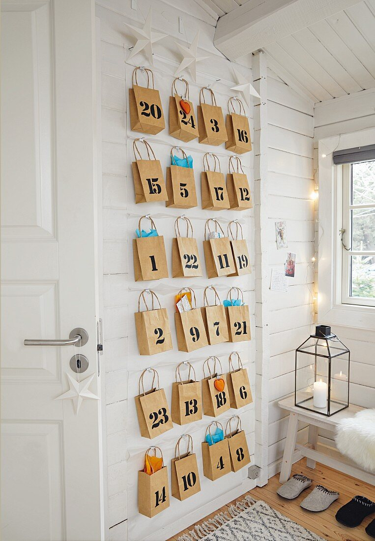 Adventskalender aus nummerierten Packpapiertüten an der Wand