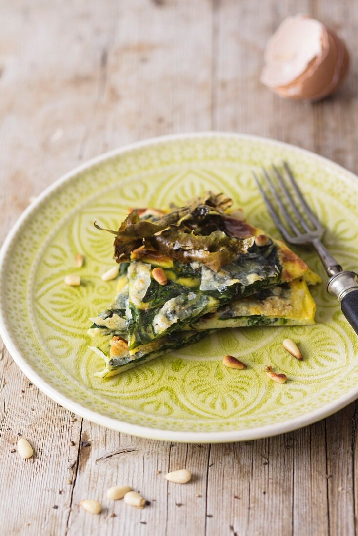 A slice of spinach tortilla with seaweed bacon and pine nuts