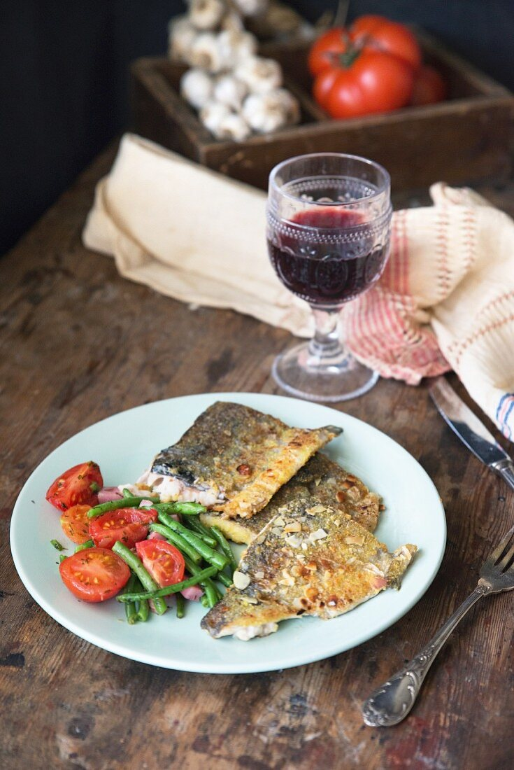 Pan-fried fish with tomatoes, garlic, green beans and a glass of red wine