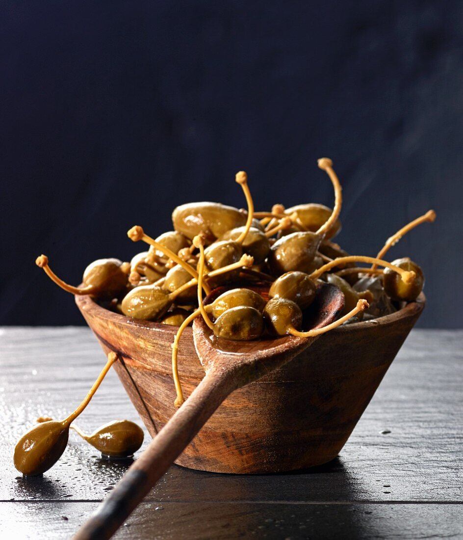 Giant capers in a wooden bowl and on a wooden spoon
