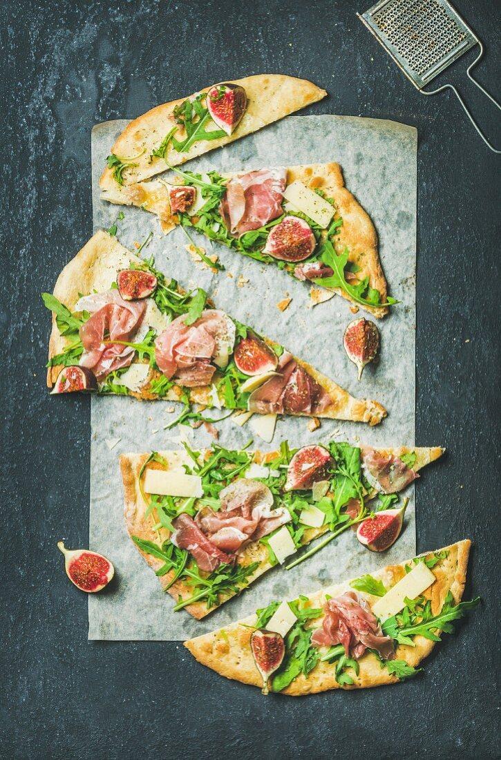 Fig, prosciutto, arugula and sage flatbread pizza cut into pieces on baking paper