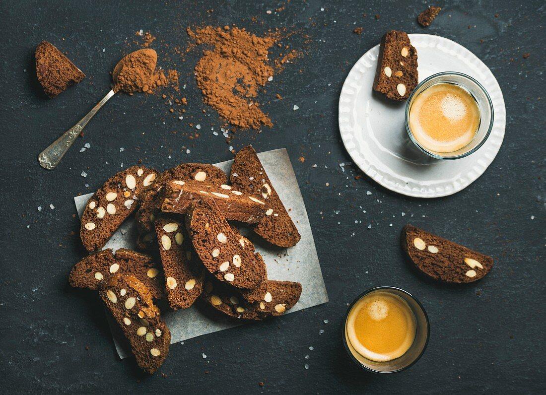 Schokoladen-Biscotti mit Meersalz-Biscotti und zwei Gläser Espresso auf dunklem Steinuntergrund