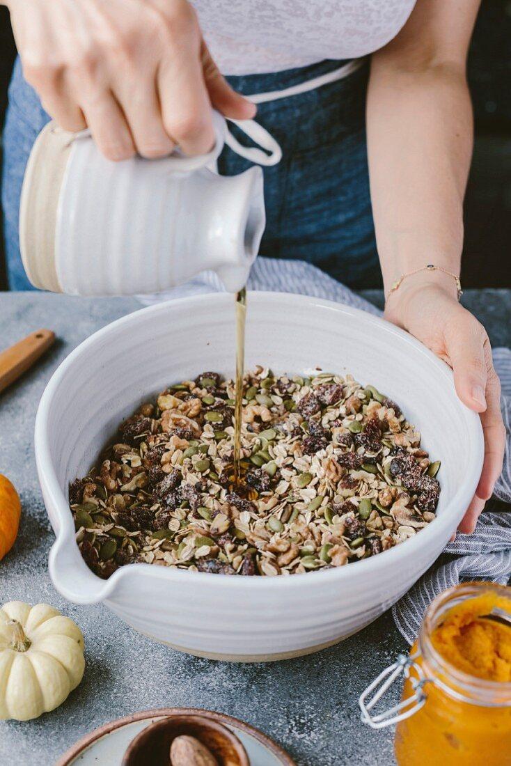 Kürbis-Cranberry-Brot zubereiten: Ahornsirup zu Nussmischung geben