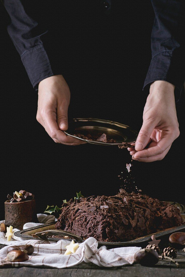 Decorating process of homemade Christmas chocolate yule log by woman's hands with chocolate chips