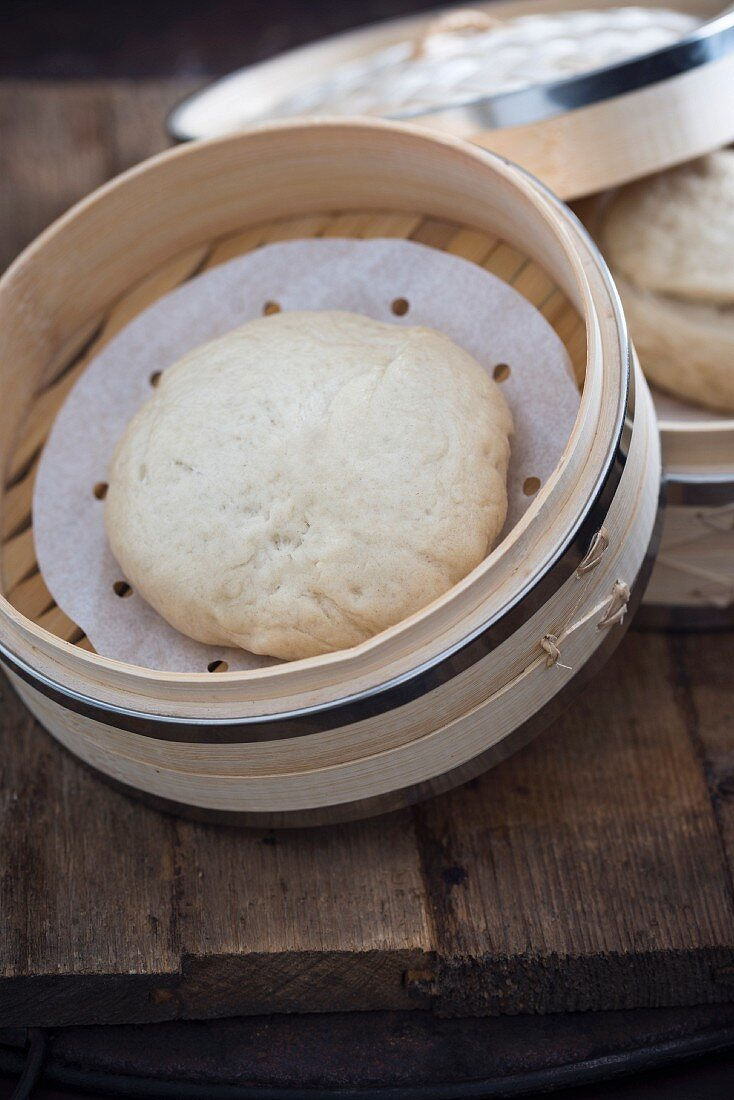 A bao bun in a bamboo steamer