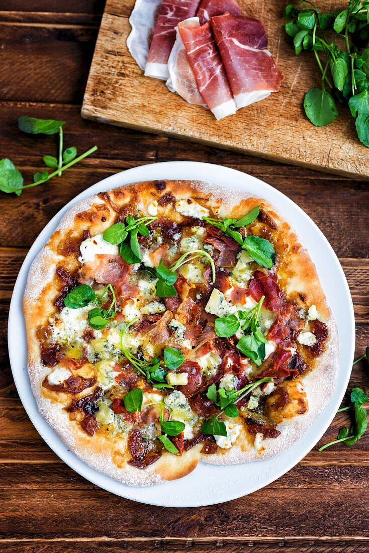 Homemade pizza with blue cheese, pancetta, onion chutney and lamb's lettuce