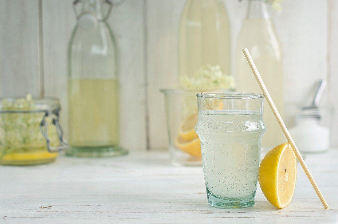 An elderflower drink in a glass with a straw and homemade elderflower cordial in bottles