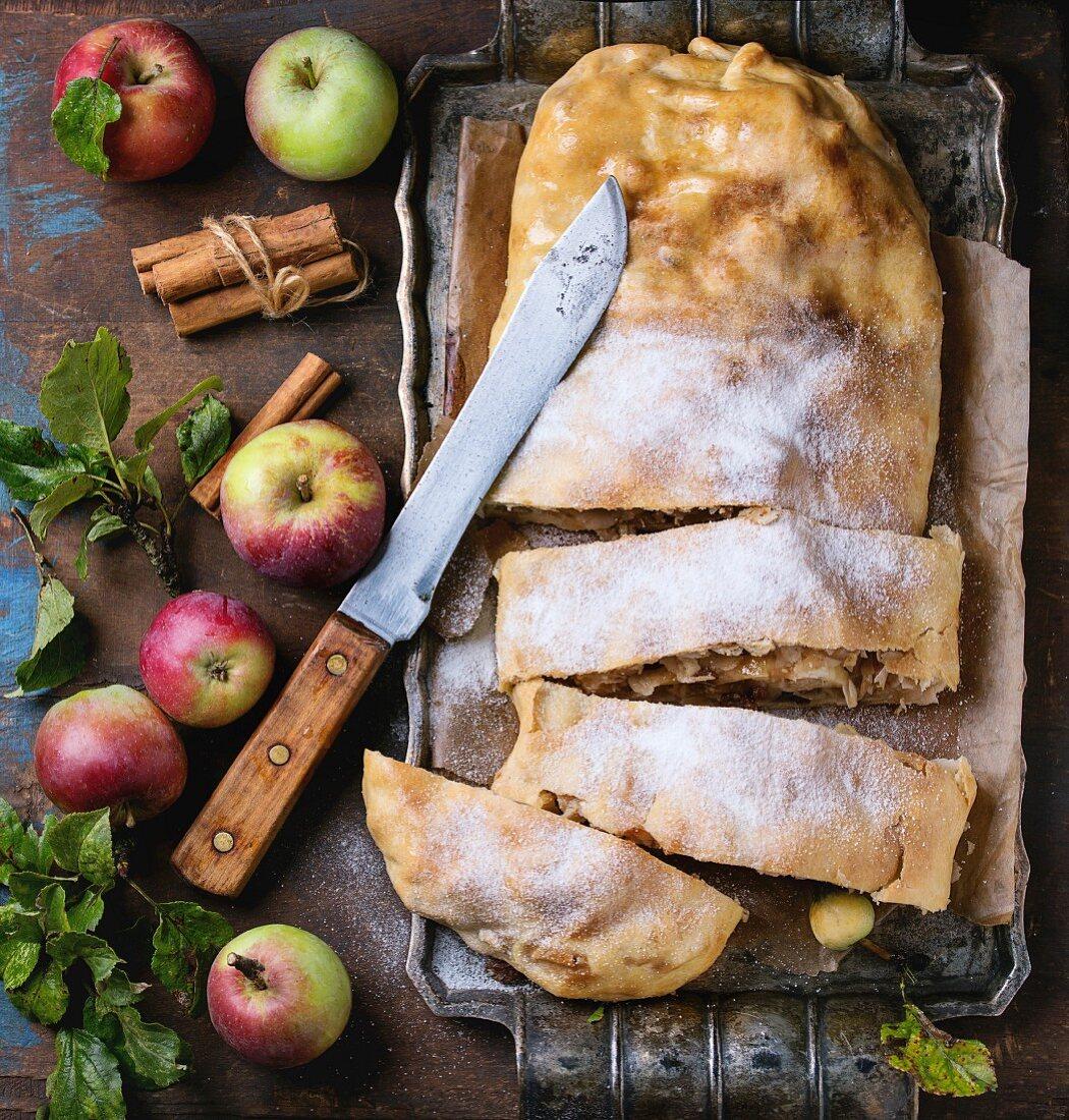 Angeschnittener Apfelstrudel mit Puderzucker, frische Äpfel, Blätter und Zimtstangen