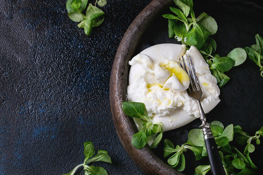 Sliced Italian cheese burrata with vintage fork, fresh corn salad and olive oil