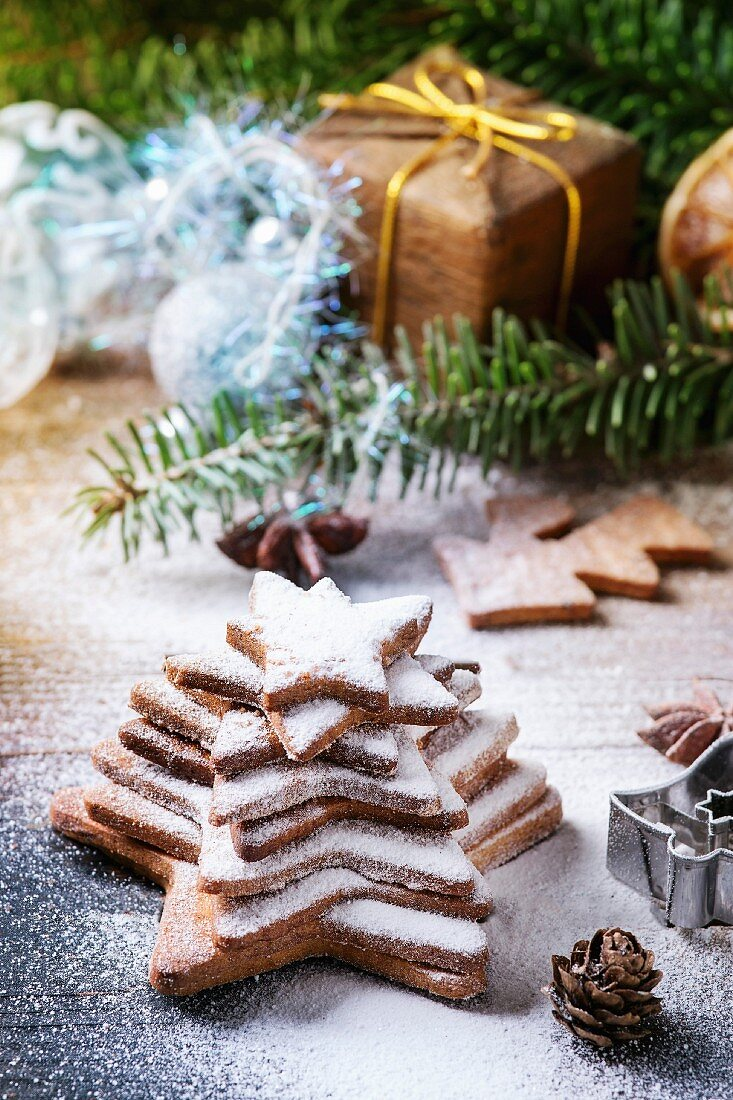 Stack of homemade Christmas shortbread star shape sugar cookies different size with sugar powder on old wooden surface