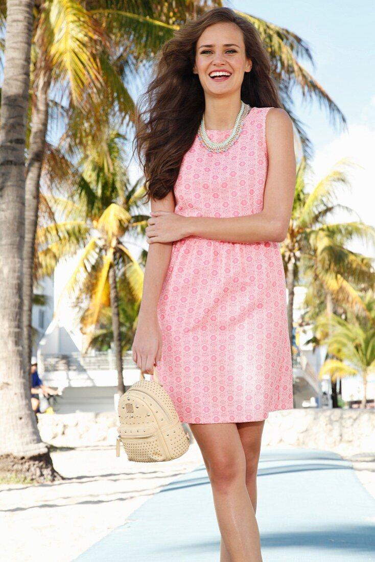 Brünette Frau in rosafarbenem, gemustertem Kleid, Statementkette und Rucksack an Strandpromenade