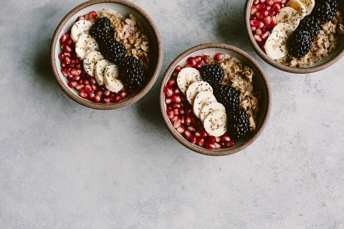 Three oatmeal bowls topped off with blackberry, banana, and pomegranate seeds