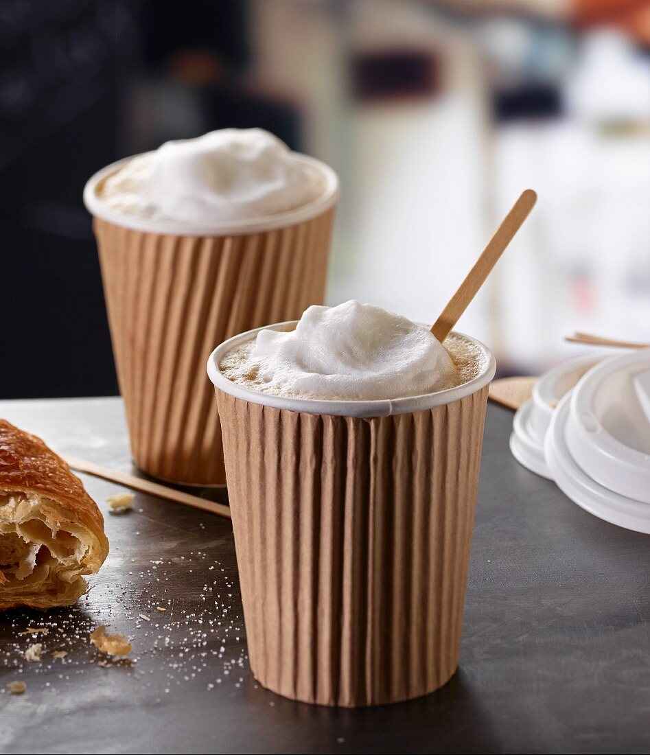 Two cappuccinos to go with a croissant
