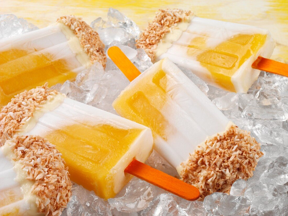 Mango and coconut ice lollies topped with white chocolate and desiccated coconut on a bed of ice cubes (close-up)