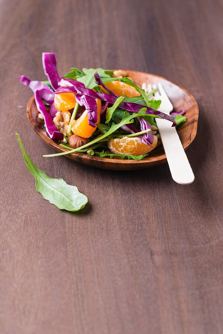 A rocket and red cabbage salad with nuts, wheat and tangerines